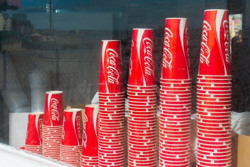Apilado encima de la Coca-Cola beba las tazas de papel en la tienda de ventanas de Brighton Pier en Brighton, Reino Unido imágenes de archivo libres de regalías