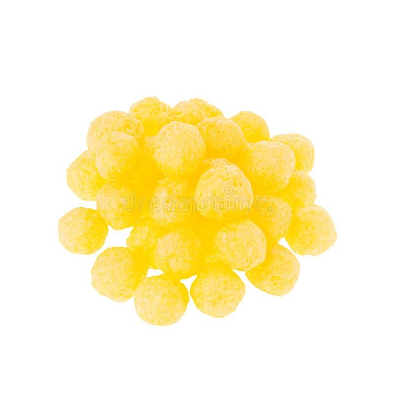 Apile las bolas amarillas de los palillos del maíz aisladas en el fondo blanco Plantilla de los alimentos de preparación rápida p fotos de archivo