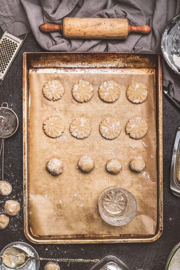 Aplaine cookies com parte inferior de um vidro bebendo na bandeja do cozimento, da preparação no fundo da mesa de cozinha com gua fotografia de stock royalty free
