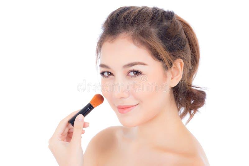 A aplicação asiática da mulher da beleza compõe com a escova do mordente isolada imagens de stock