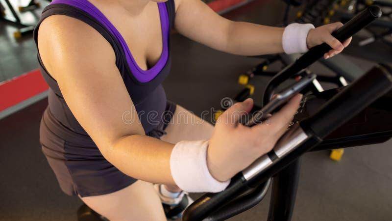 Aplicação da aptidão, bicicleta de exercício obeso da equitação da menina e dispositivo do móbil do desdobramento imagens de stock