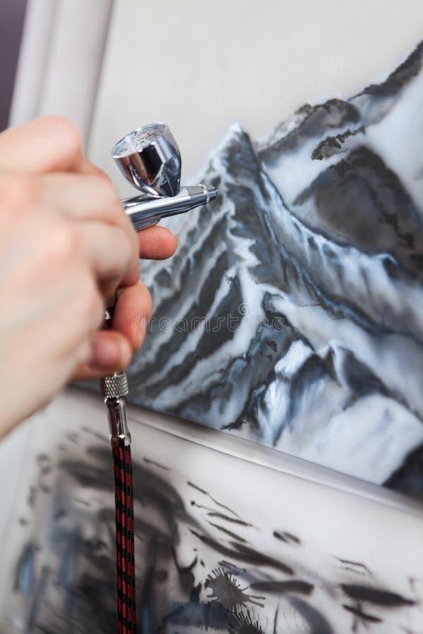 A aplicação da cor com o aerógrafo que pulveriza com o ar comprimido, fim acima da vista imagem de stock