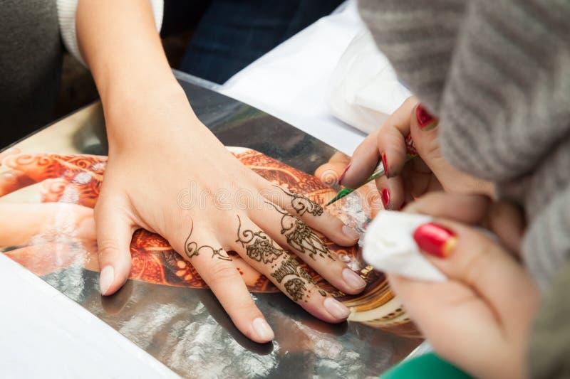 Aplicação de Mehndi na mão da mulher, decoração da pele imagens de stock