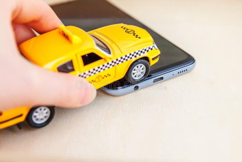 Aplicação de smartphone do serviço de táxi para pesquisa online chamando e marcando o conceito de cab Mão com carro de brinquedo  imagem de stock royalty free