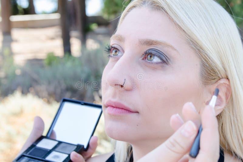 A aplicação profissional do maquilhador compõe exterior imagens de stock royalty free