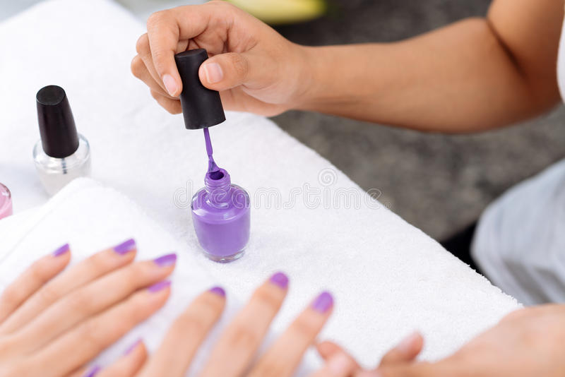 Aplicación de esmalte de uñas púrpura imagen de archivo libre de regalías