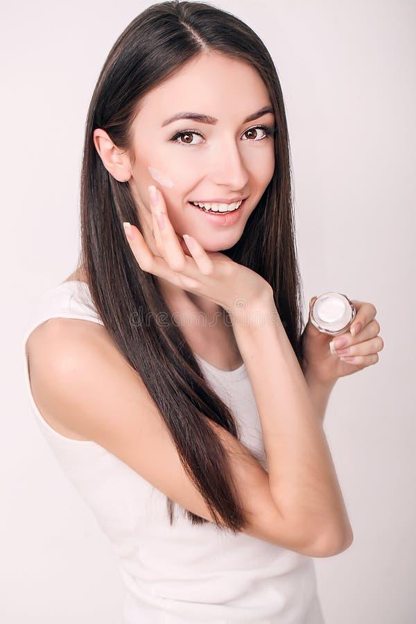 Aplicación de la crema cosmética Una mujer joven hermosa que aplica la crema hidratante de la cara Cuidado de Scine de la cara y  fotografía de archivo libre de regalías