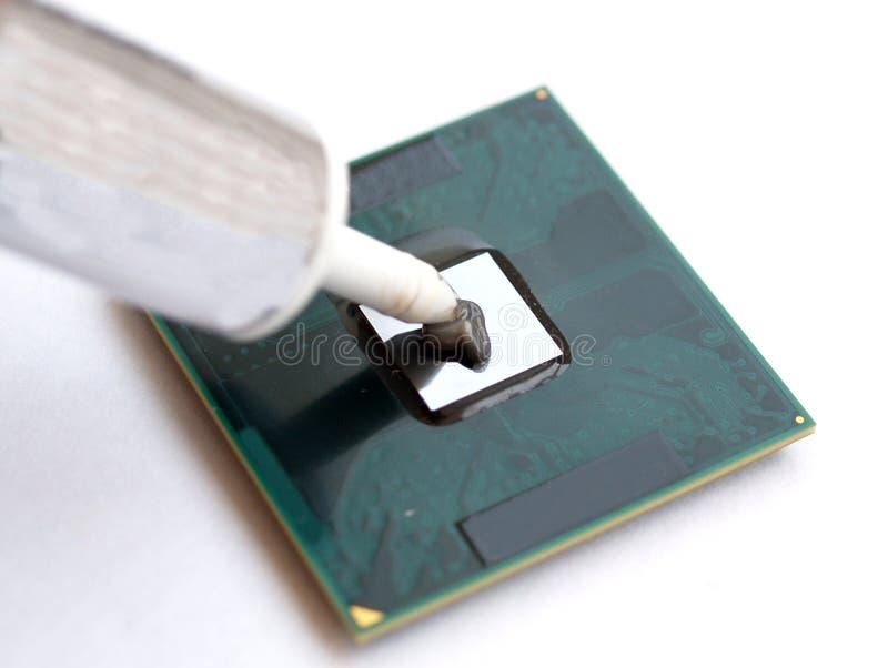 Aplicación de la grasa termal sobre un procesador de la CPU del ordenador imagenes de archivo