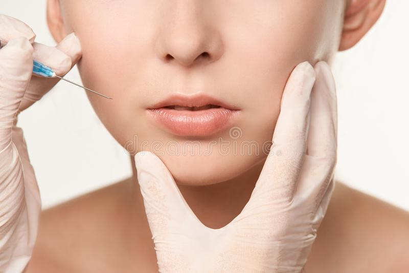 Aplicación de procedimiento médico plástico de la cosmetología Modelo de la muchacha Mano fuerte fotos de archivo