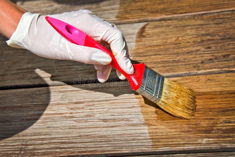 Aplicación del barniz protector en la madera imagen de archivo libre de regalías