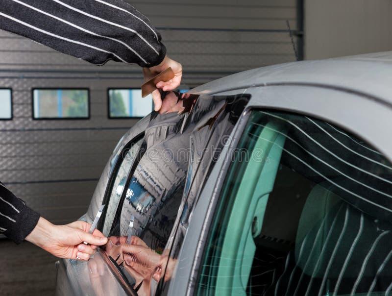 Aplicación teñiendo la hoja en una ventanilla del coche imagenes de archivo
