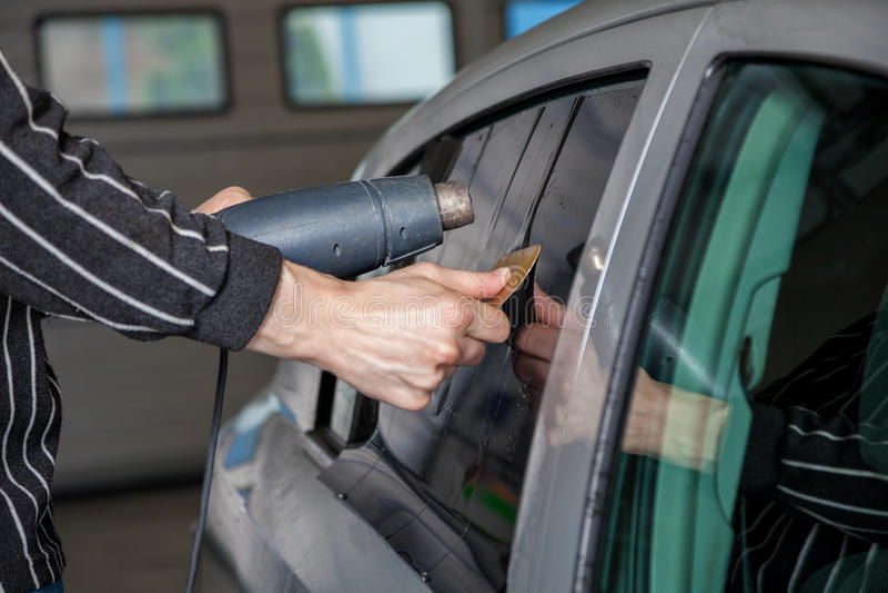 Aplicación teñiendo la hoja en una ventanilla del coche imágenes de archivo libres de regalías