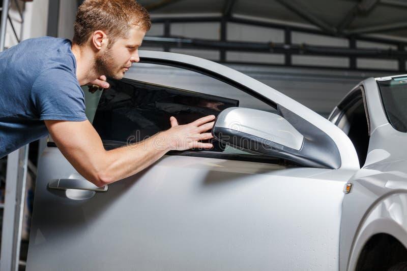 Aplicación teñiendo la hoja sobre una ventanilla del coche fotografía de archivo