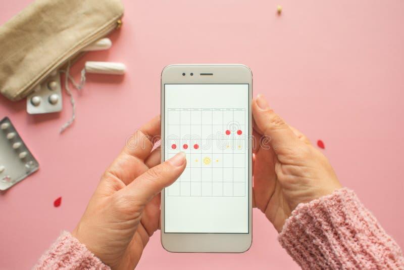 Aplicaci?n m?vil para seguir su ciclo menstrual y para las marcas PMS y el concepto cr?tico de los d?as imagen de archivo
