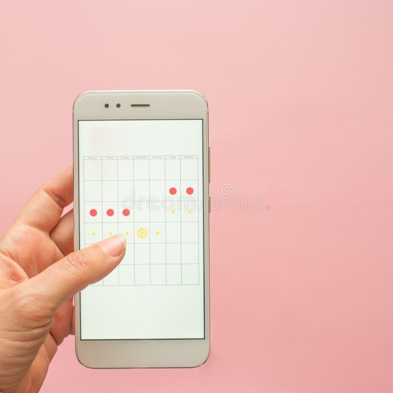 Aplicaci?n m?vil para seguir su ciclo menstrual y para las marcas PMS y el concepto cr?tico de los d?as foto de archivo libre de regalías