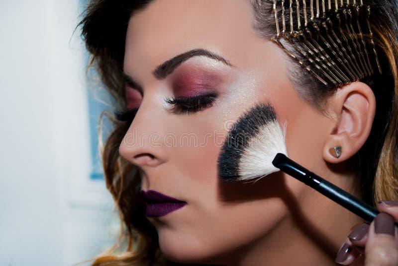 Aplicando a composição com a escova na cara da menina da beleza no estúdio fotos de stock