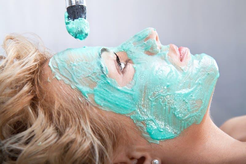 Aplicando a máscara de beleza da lama na face da mulher fotografia de stock royalty free