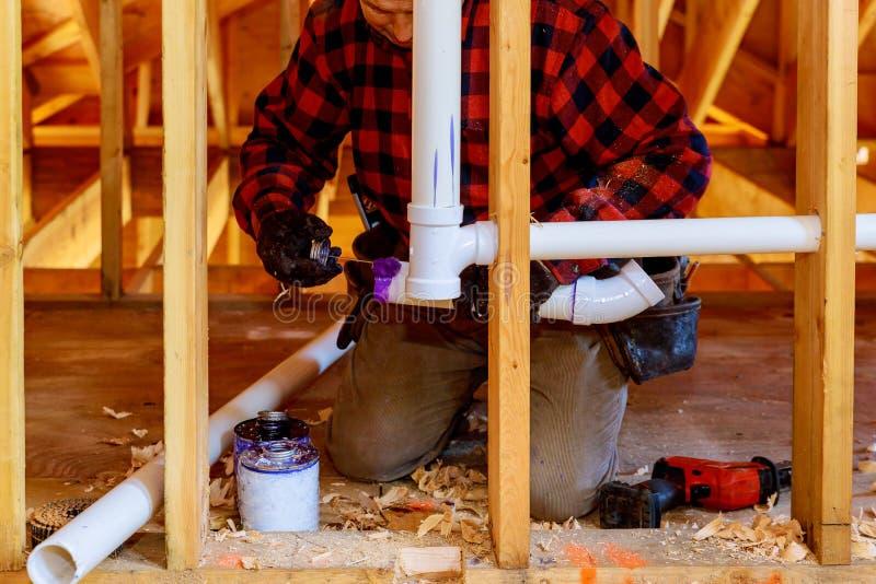 Aplicando o dreno da tubulação do encanador e o sistema de encanamento do respiradouro na construção nova da casa fotos de stock royalty free