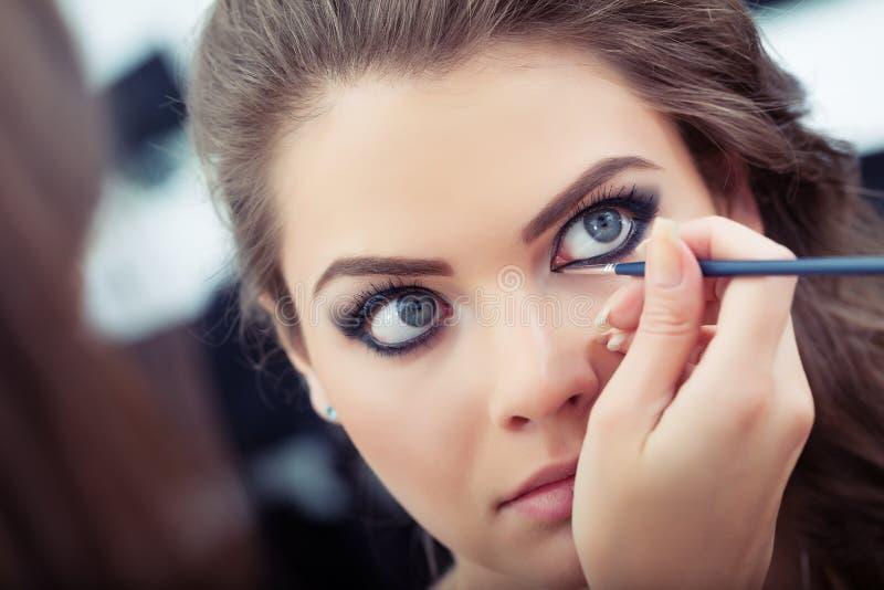 Aplicando o eyeliner líquido fotografia de stock
