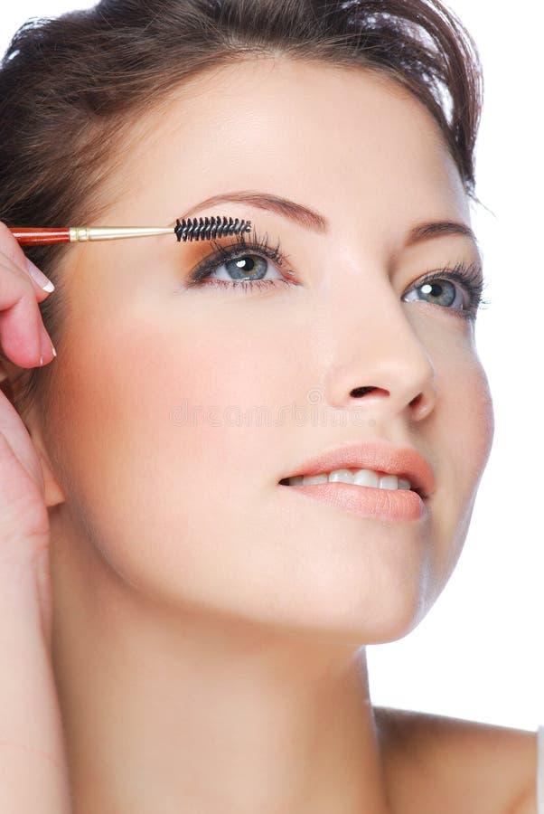 Aplicando o mascara usando a escova do chicote foto de stock