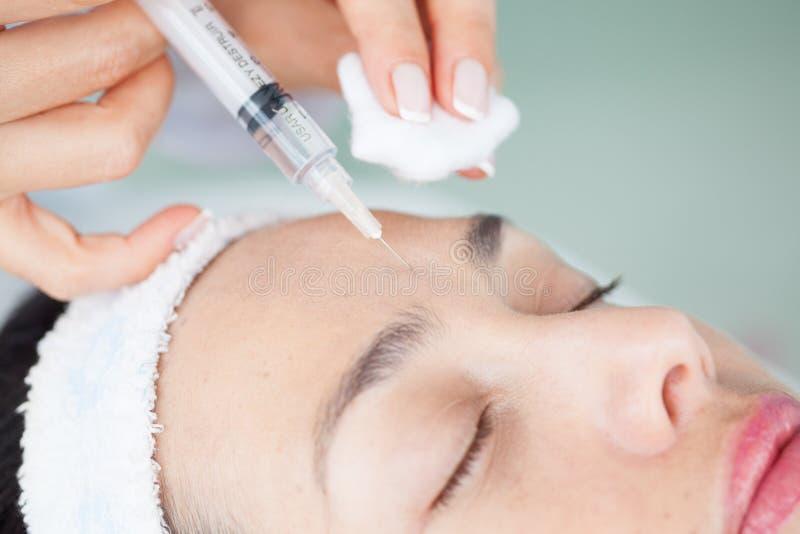 Aplicando um tratamento facial usando uma seringa foto de stock royalty free
