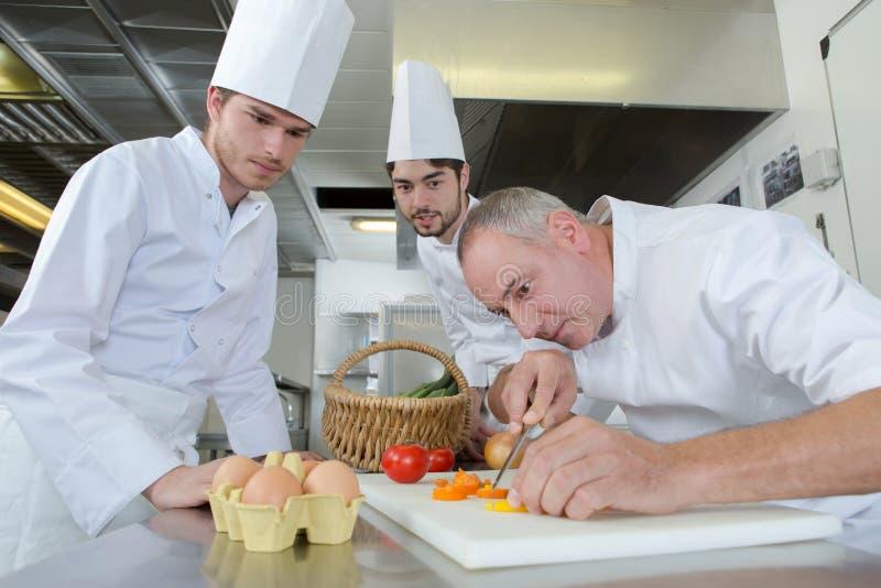 Aplikanci ogląda naczelnego szefa kuchni garnirowania naczynie zdjęcia stock
