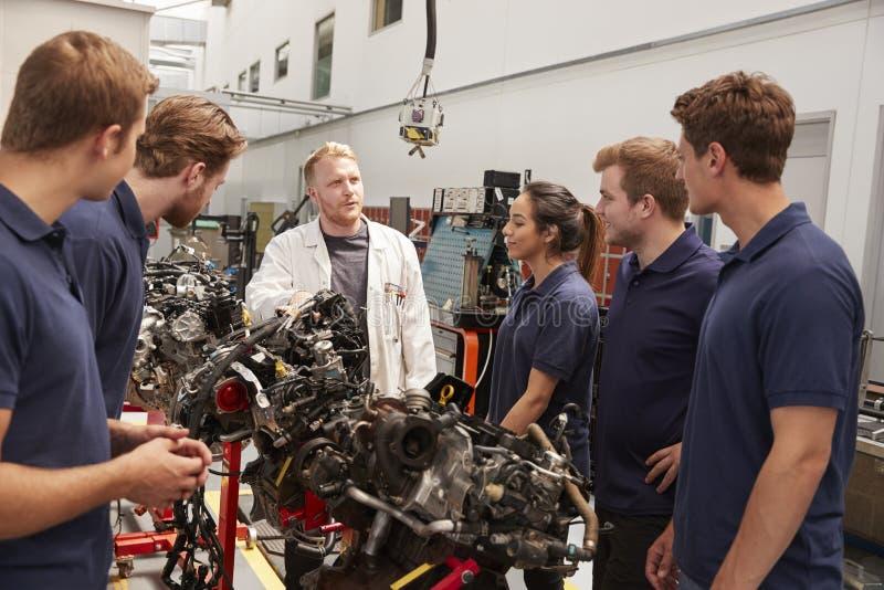 Aplikanci studiuje samochodowych silniki z mechanikiem, zamykają up fotografia stock