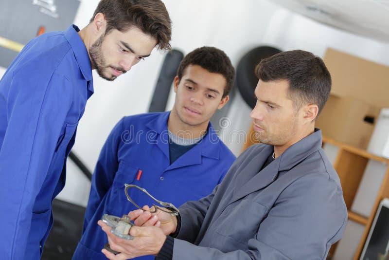 Aplikantów mechanicy pracuje w auto remontowym sklepie zdjęcia royalty free