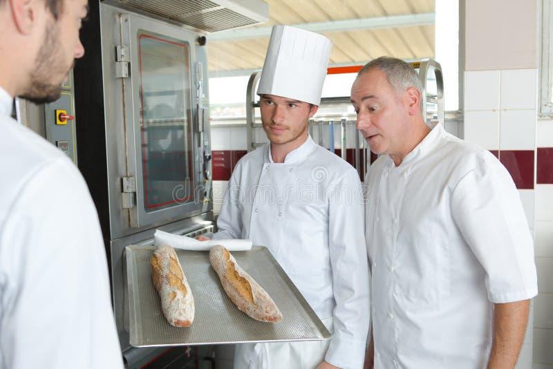 Aplikanta piekarz w bakehouse z taca chlebem obrazy stock