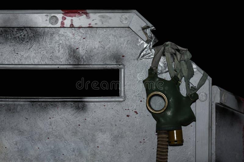 Apocalypse, Gasmaske, die an einem Bunker auf einem schwarzen Hintergrund hängt stockfotos