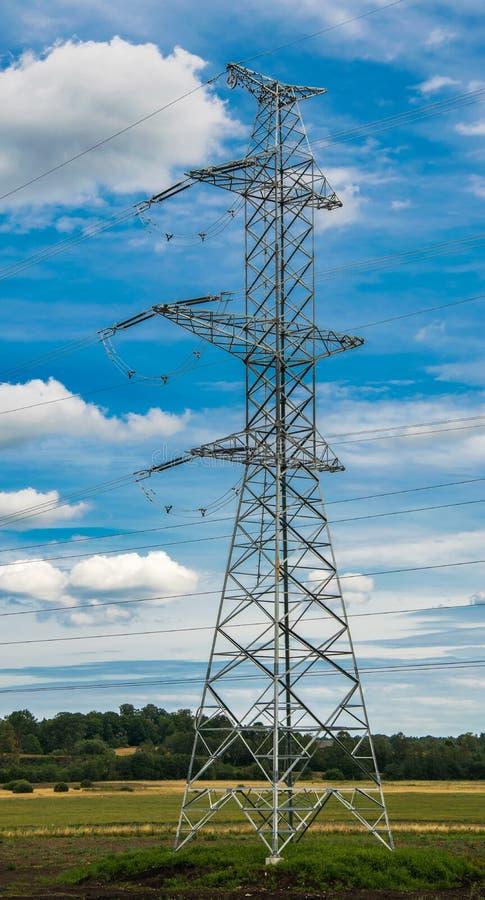 Apoia linhas elétricas de alta tensão contra o céu azul com as nuvens Indústria elétrica foto de stock royalty free