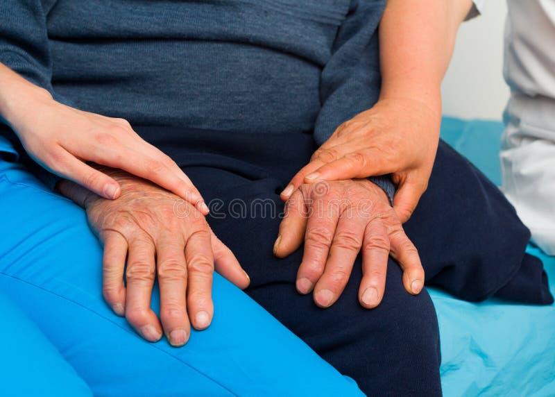 Apoiando as pessoas idosas com doença de Parkinson foto de stock