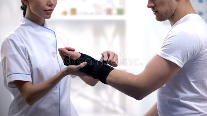 Apoio de pulso ao paciente masculino, inflamação comum da fixação da enfermeira, reabilitação fotos de stock royalty free