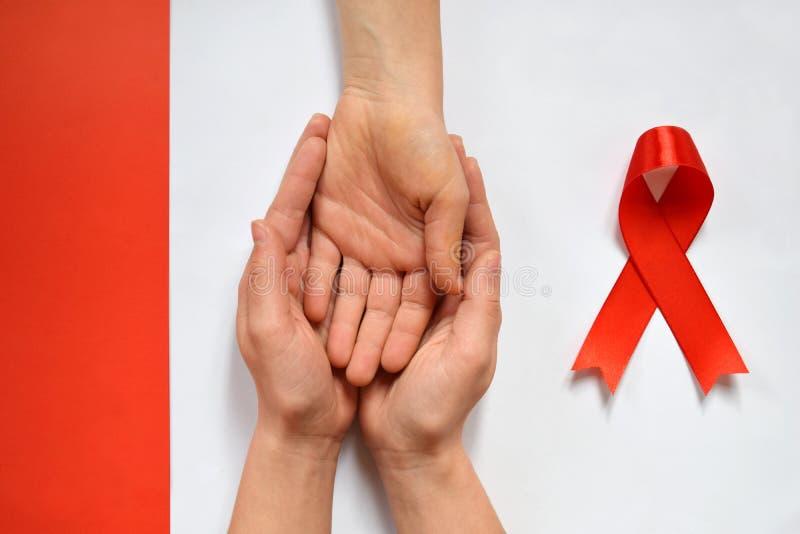 Apoio paciente com diagnóstico do SIDA do VIH As mãos das mulheres que guardam a mão Dia Mundial do Sida e fita vermelha Notícia  imagens de stock royalty free
