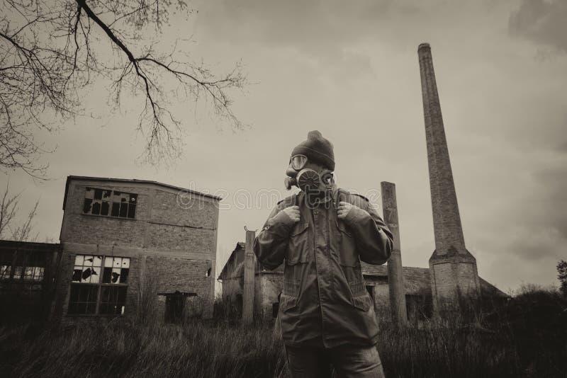 Apokalyptisk överlevande för stolpe i gasmask och ryggsäck royaltyfria bilder