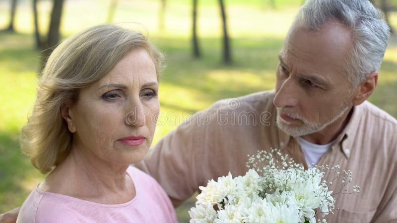 Apologizing man giving flowers to woman, crisis in relations, couple quarrel stock image