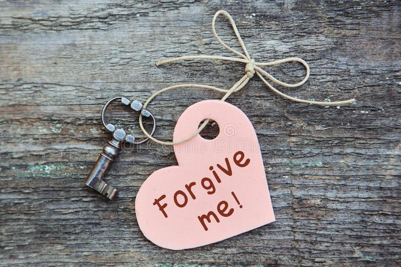 An apology card with the words forgive Me.  A heart with an antique key lies together on a wooden Board. The concept of royalty free stock photography