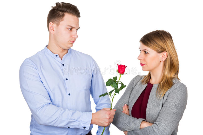 Apology gift. Picture of a young men giving her girlfriend a red rose as an apology royalty free stock image