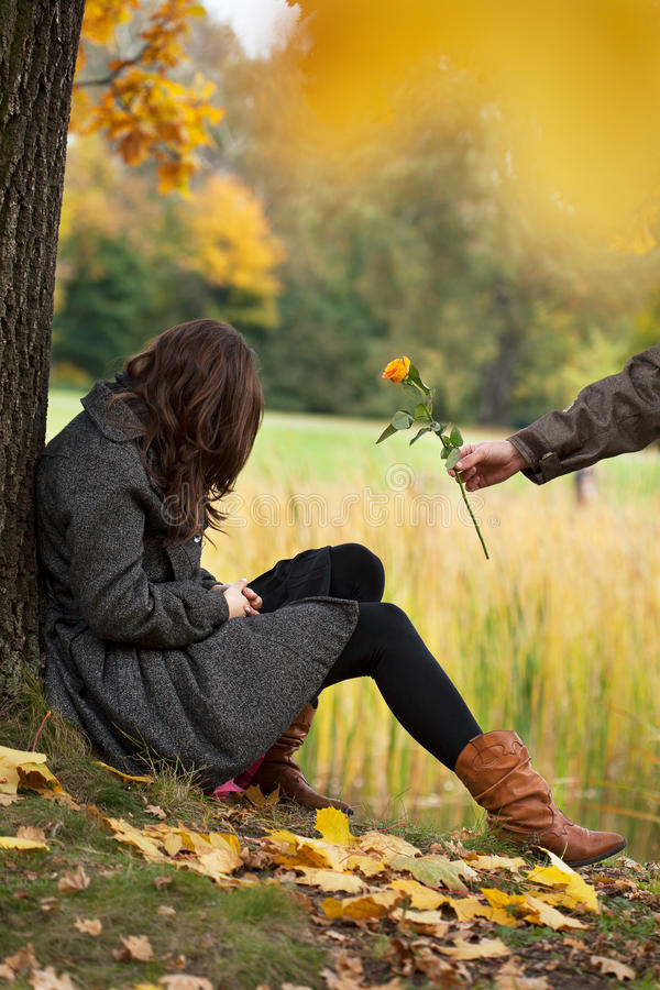 Apology after quarrel. Young man apologizing girl after quarrel in park royalty free stock photo