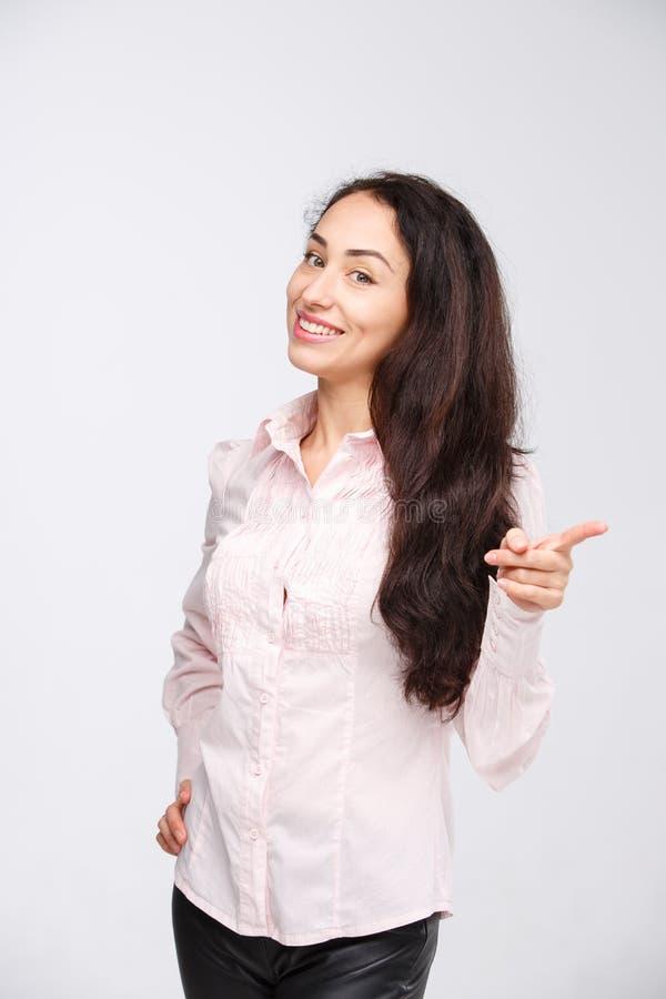 Apontar de sorriso da mulher acima de mostrar o espaço da cópia Mulher de negócios profissional nova bonita isolada no fundo bran imagens de stock