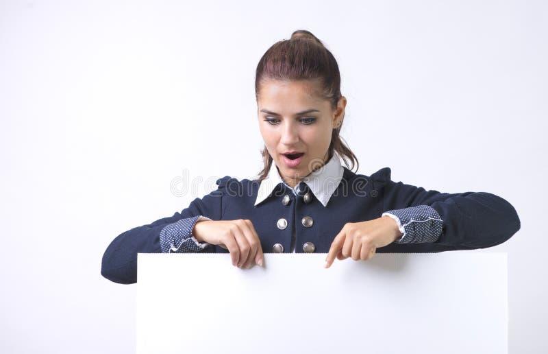 Apontar entusiasmado da mulher na placa vazia vazia do sinal do papel do quadro de avisos Mulher de negócio nova isolada no fundo foto de stock royalty free
