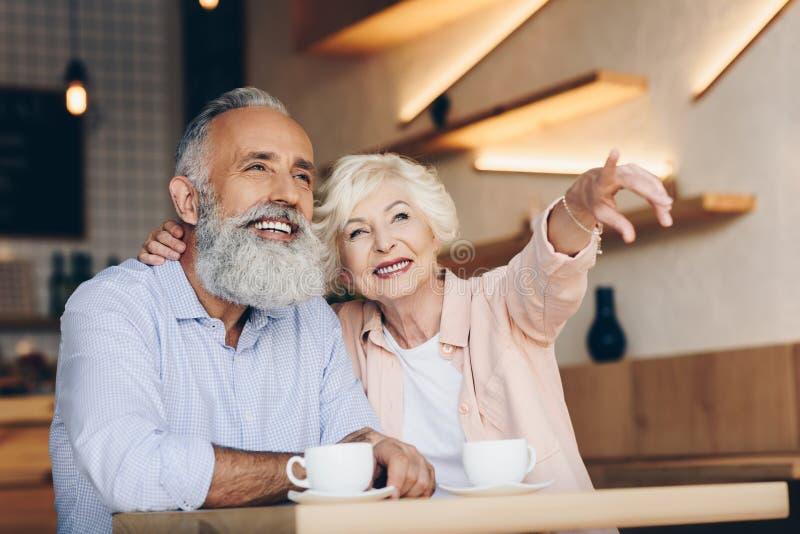 apontar superior de sorriso da mulher ausente ao beber o café junto com o marido imagens de stock