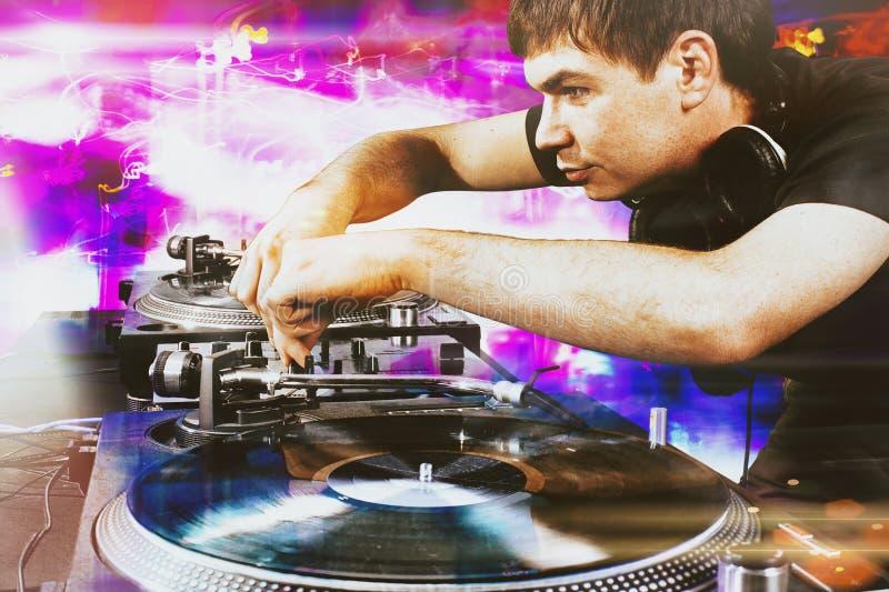 Aporree a DJ que juega música de mezcla en placa giratoria del vinilo fotografía de archivo