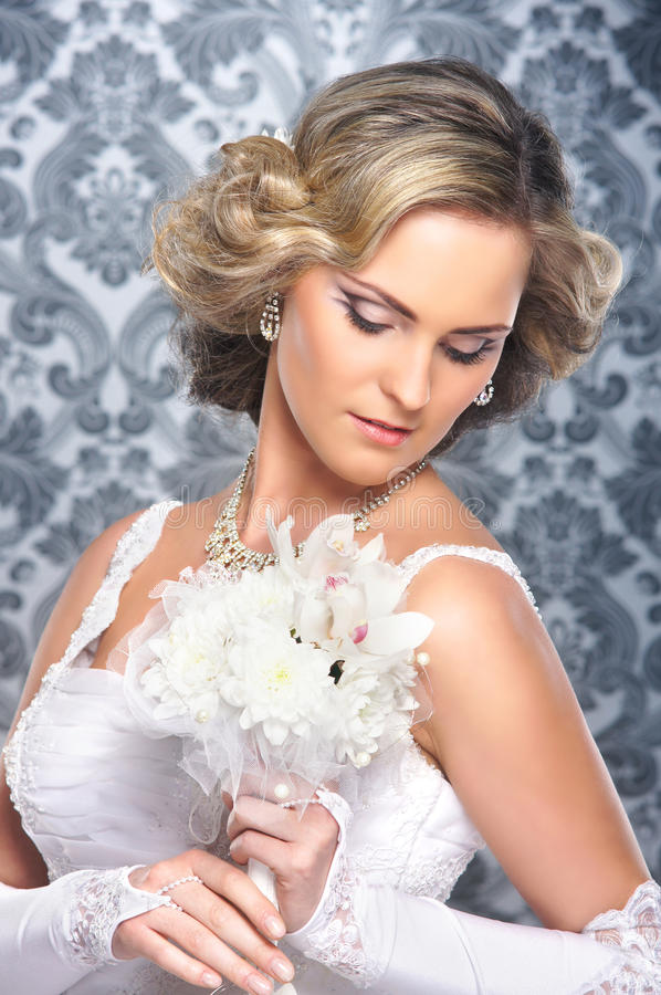 APortrait of a young blond bride posing in a white dress royalty free stock image