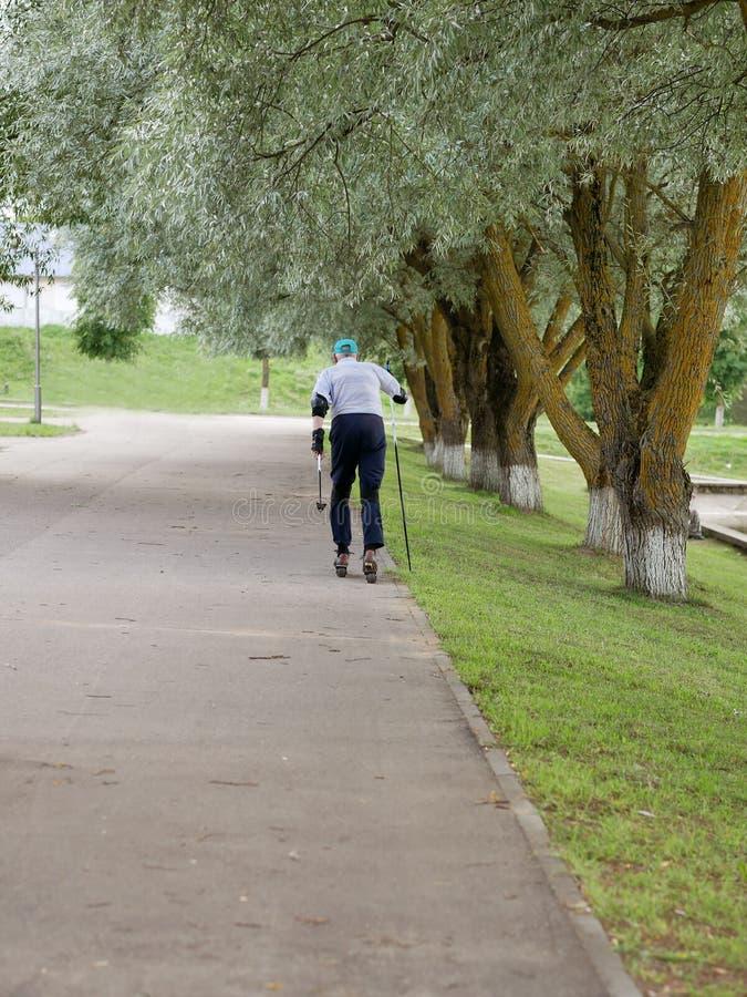 Aposentado ativo que rollerblading e que faz voltas extremas O outono anda no ar fresco Pessoas adultas ativas imagem de stock