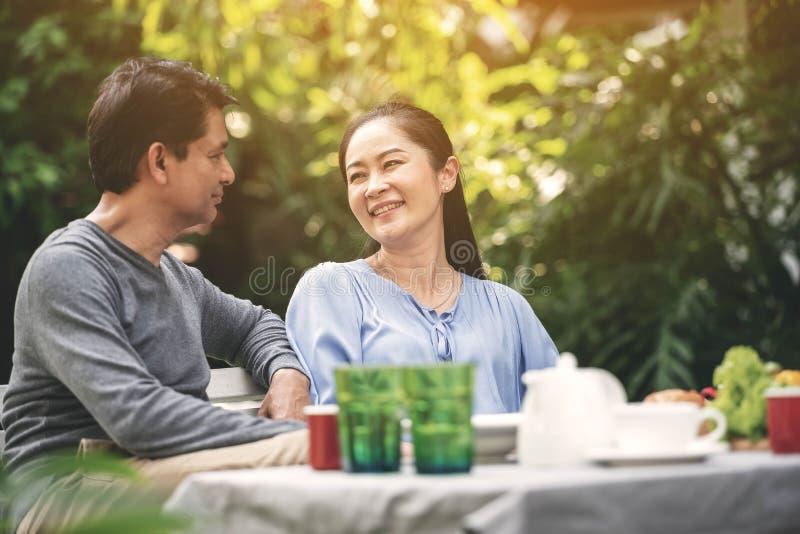 Aposentadoria bonita asiática dos pares que tem uma felicidade que fala durante o jantar no quintal Família feliz após a aposenta imagens de stock
