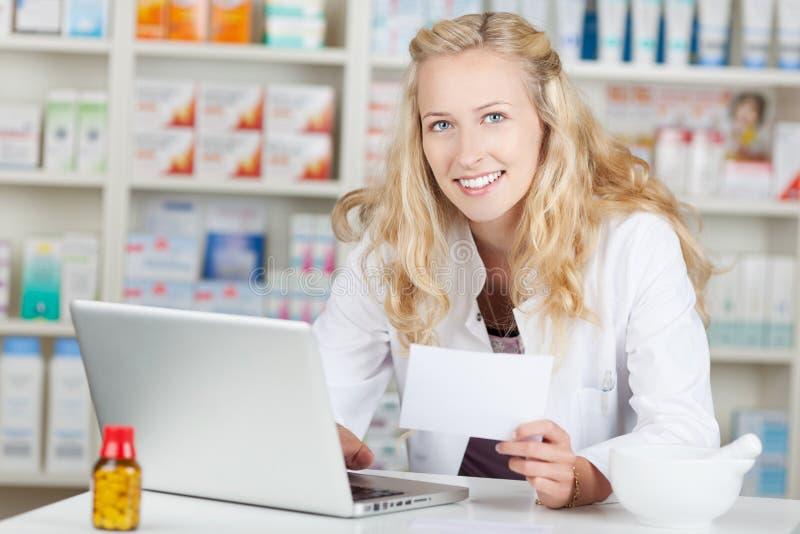 Apotekare Holding Prescription Paper, medan genom att använda bärbara datorn på Coun arkivfoto