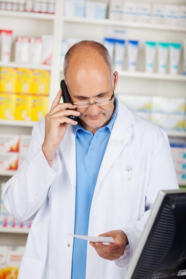 Apotekare Holding Prescription Paper, medan genom att använda den sladdlösa telefonen royaltyfria bilder