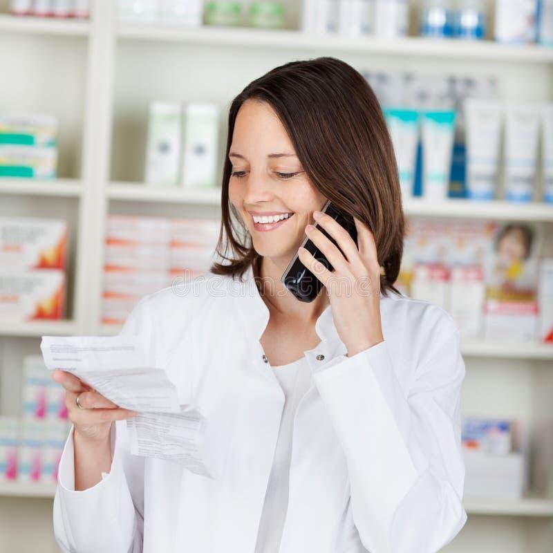 Apotekare Holding Prescription Paper, medan genom att använda den sladdlösa telefonen arkivbilder