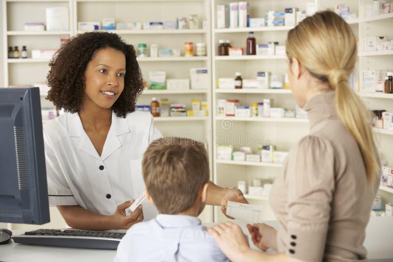 Apotekare i apotek med modern och barnet royaltyfria bilder